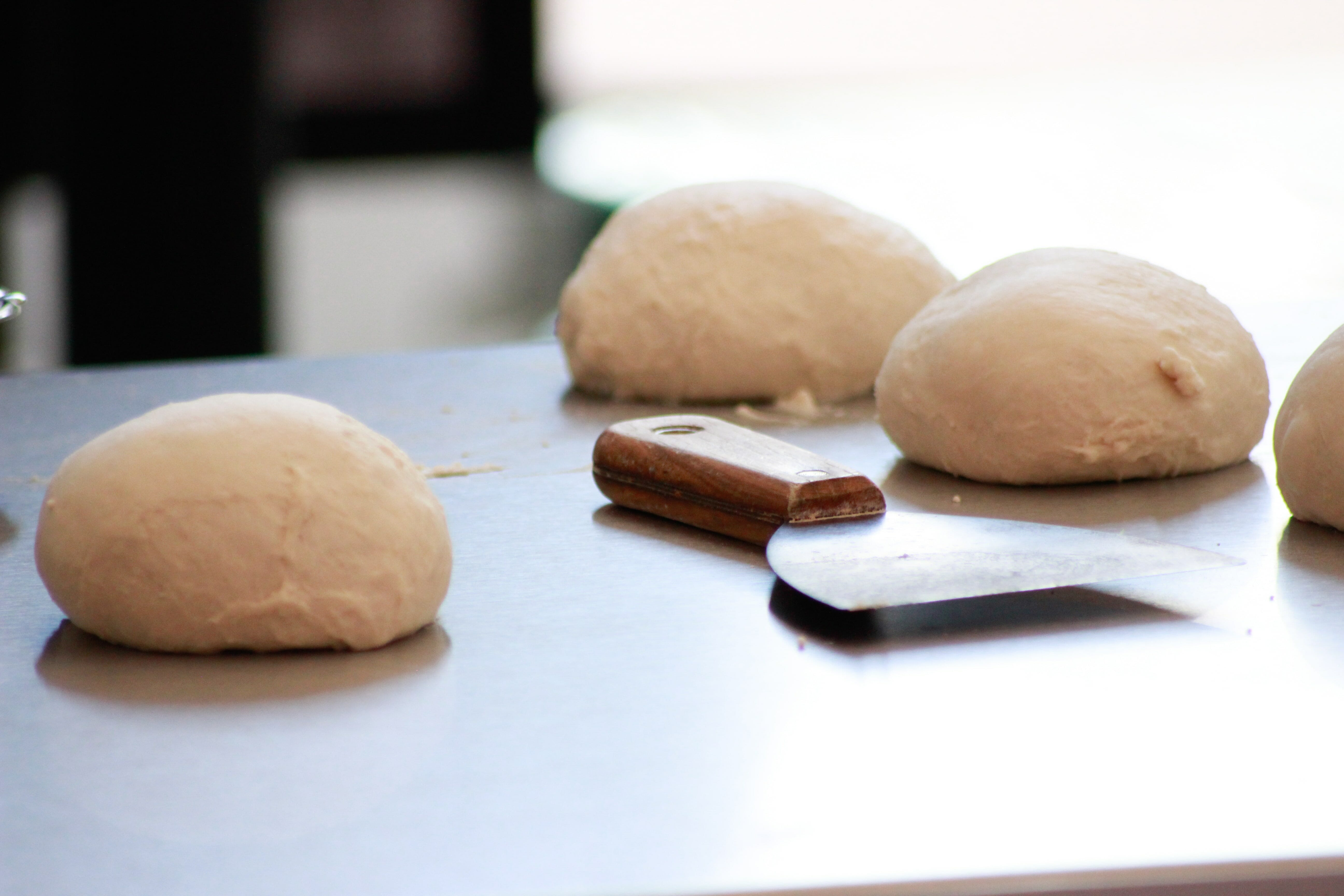 Dough Balls resting on a table next to dough cutter