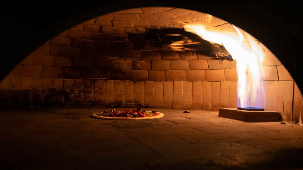 Pizza cooking by a gas powered fire in a large neapolitan brick oven