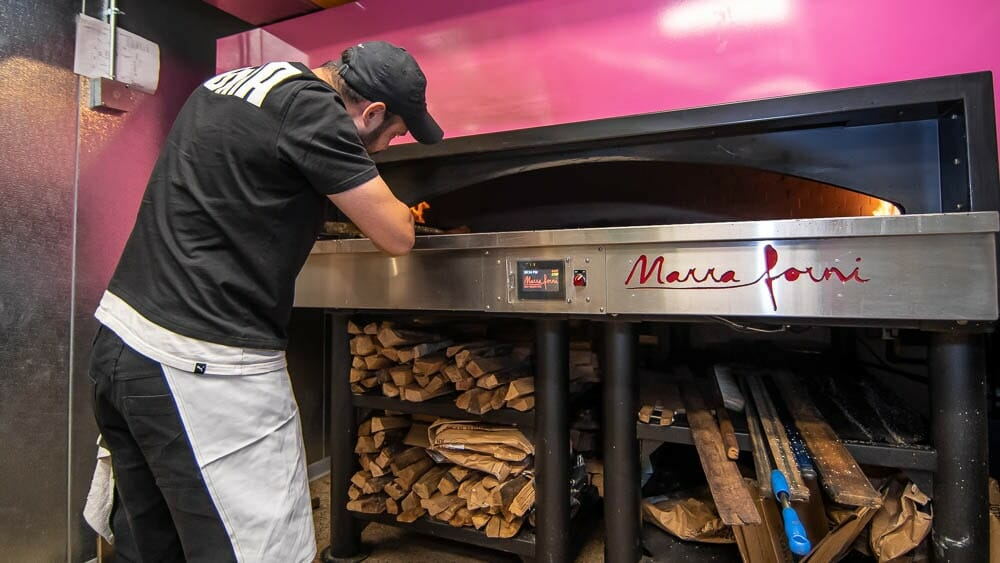 Pink Wood and Gas fired Marra Forni brick oven being operated by Bagel Chef