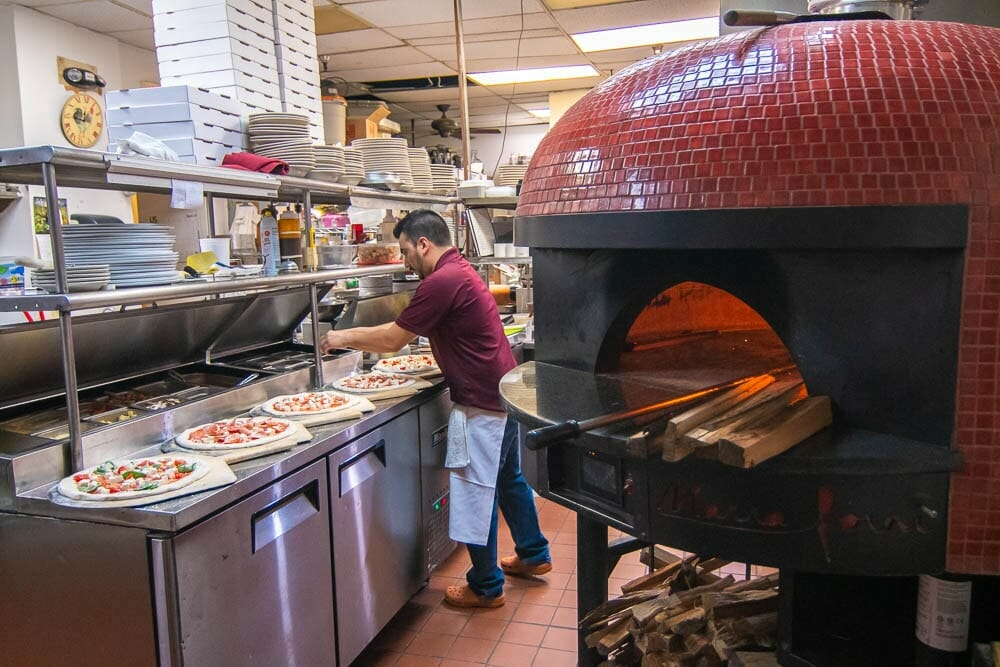 Italian Pizza Chef Preparing Multiple Pizzas Before Cooking In Red Wood Fired Brick Oven From Marra Forni