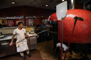La Posta Restaurant Indoors with Chef Baking Pizza In Wood Fired Red Tiled Brick Oven