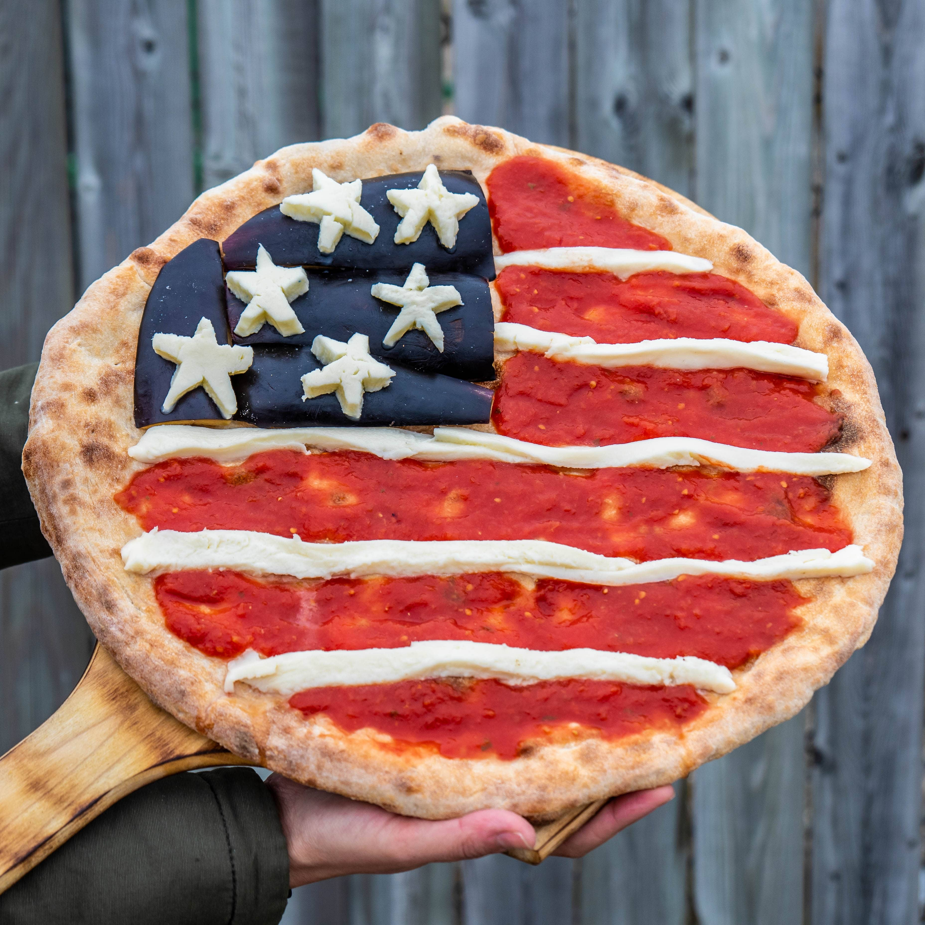 American Flag themed pizza with eggplant, cheese starts, and tomato sauce