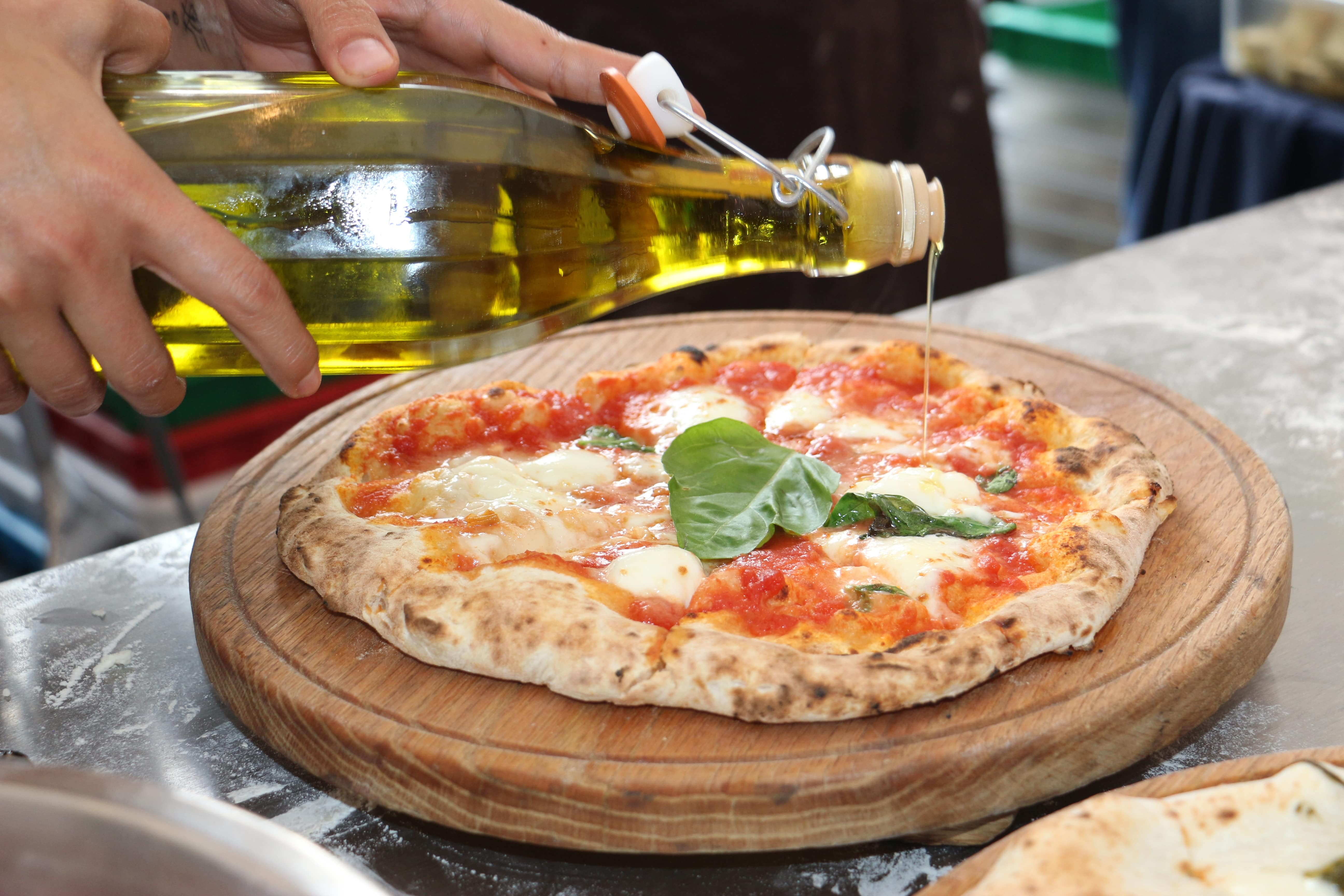 Hand Pours extra virgin olive oil on freshly baked margherita pizza