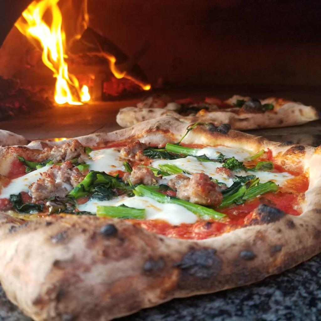 Fresh pizza with mozzarella, greens and meats in wood fire brick oven